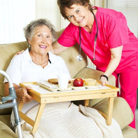 caregiver serving food for the elder woman