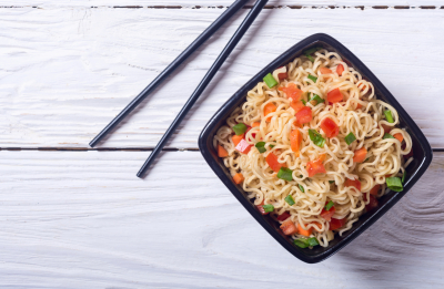 Noodles in bowl with tomatoes and onion